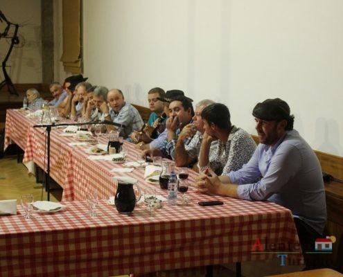 Homens a beber, comer e cantar.