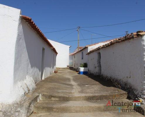 Rua de cimento com casas brancas.