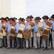 Homens com trajes na rua a levar mantas de lã de ovelha - Ganhões