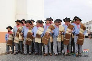 Homens com trajes na rua a levar mantas de lã de ovelha