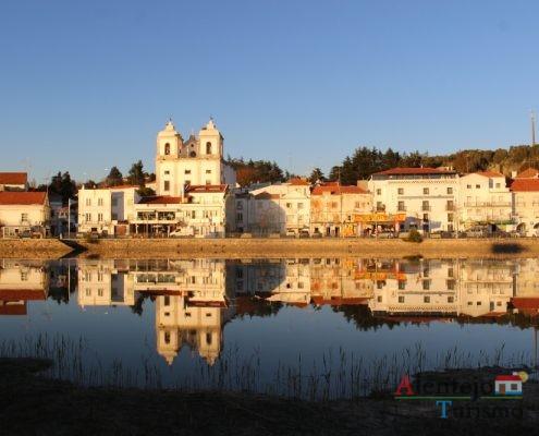 Igreja e casas refletidas no rio