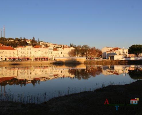 Sapais e cidade refletida no rio