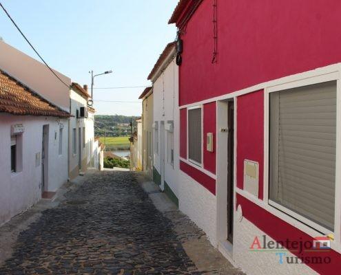 Rua de casas brancas e casa rosa forte