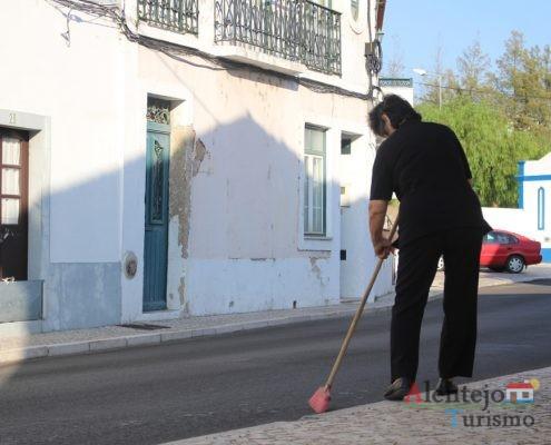 Mulher a varrer a rua
