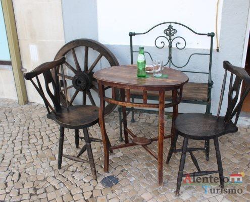 mesa, cadeiras e banco feito a partir de uma cama de ferro