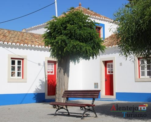 Casas com barra azul e porta vermelha e árvore