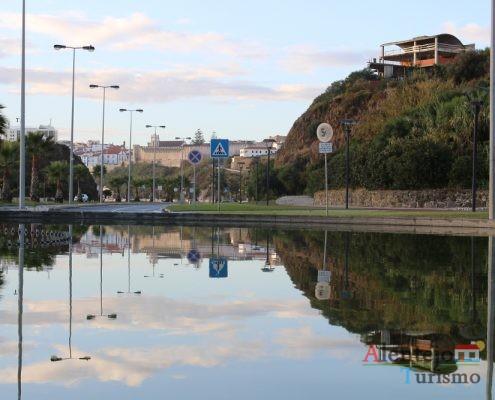 Cidade e rochedo refletido na água