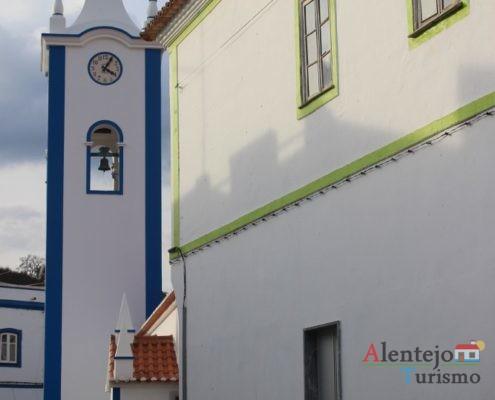 Torre da igreja e casa tradicional com barras verde