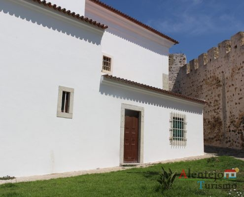 Muralha de castelo, casa branca com porta e janela