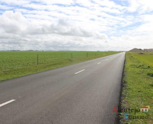 Rota M1109 : estrada, campo verde e céu com nuvens