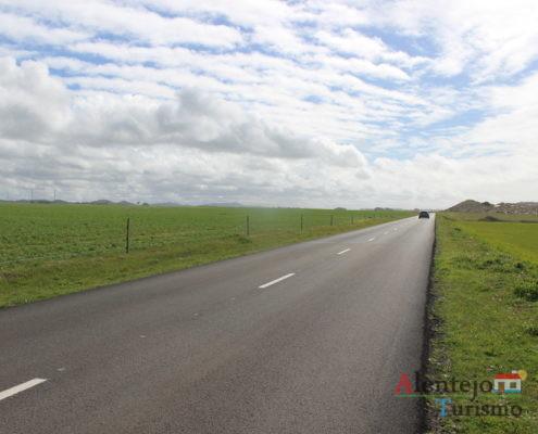 Estrada, campo verde e céu com nuvens