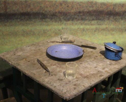 Prato azul, talheres e marmita sobre a mesa