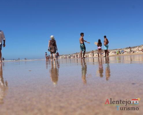 Praia do Malhão - Pessoas refletidas na água da na praia