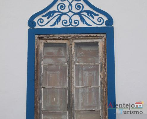 Janela de madeira e barra floreada a azul