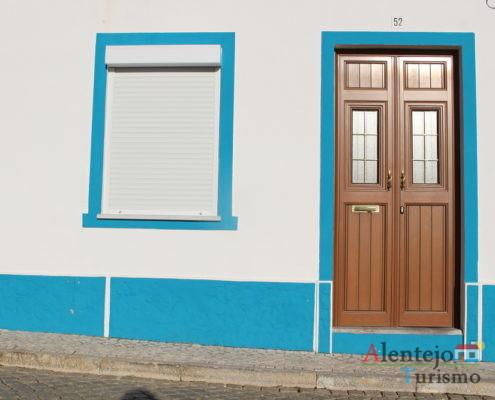 Porta castanha em casa com janela e barra azul