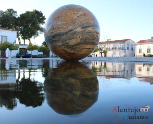 Reflexo de casas e esfera na água