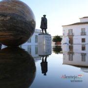 Reflexos na água de estátua, casa e esfera