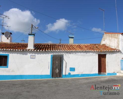 Casa típica com barra azul claro, chaminé e porta castanha