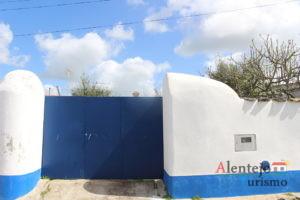 Muro branco com barra azul e portão azul