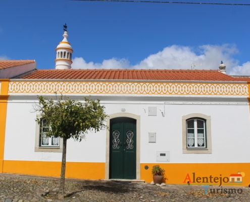 Casa de barras amarelas e bordadura no telhado