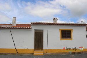 Casa típica caiada com barra amarela.