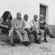 Homens e mulher sentados nos bancos de rua