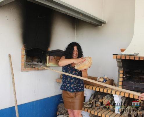 Mulher a retirar pão do forno