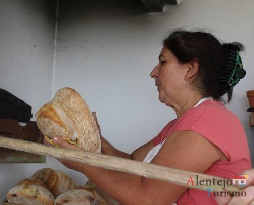 Mulher a retirar o pão do forno