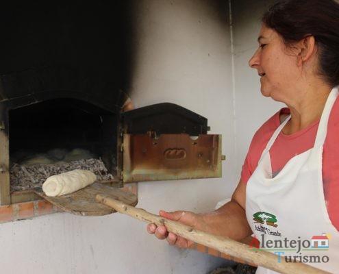 Mulher a colocar o pão com chouriço no forno