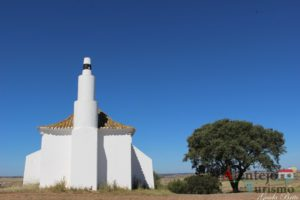 Igreja com marco geodésico e árvore.