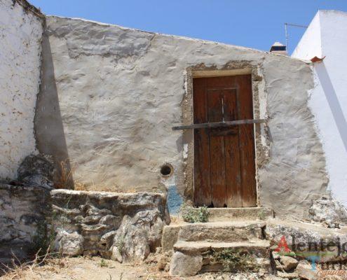 Casa, bancos de pedra e porta com tranca.