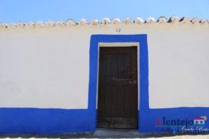 Casa com porta castanha e barras azuis.