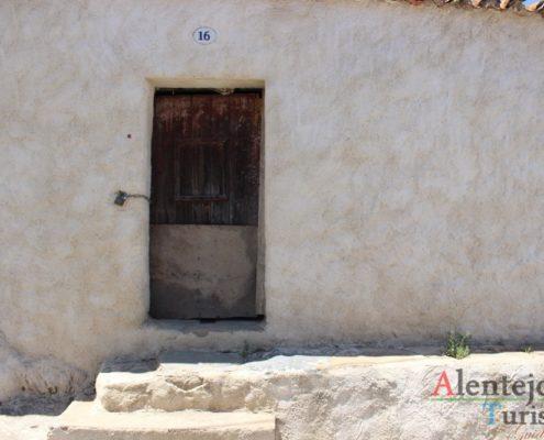 Porta antiga e banco de pedra na entrada da casa.
