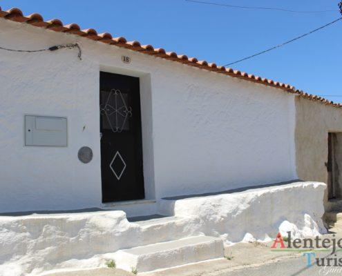 Casa branca com porta castanha.