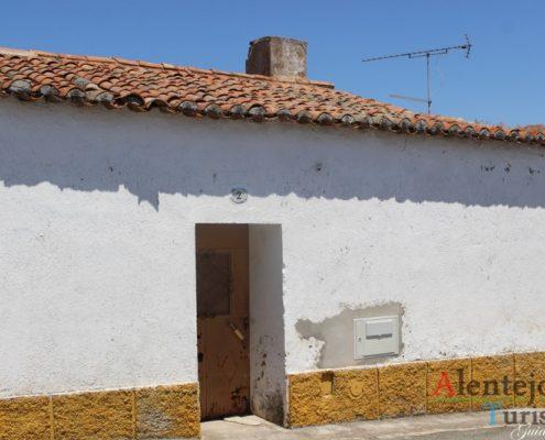 Casa com porta castanha e barra amarela.